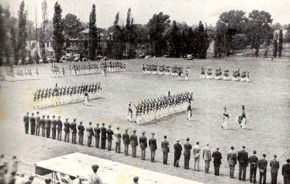 The cadets and graduates drill on the parade ground before a reviewing body of faculty and alumni of the college, while friends in the grandstand watch. - Photo from The Delaware County Advocate, June 1942