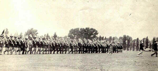 P. M. C. alumni perform the traditional broom drill before the reviewing stand. - Photo from The Delaware County Advocate, June 1942